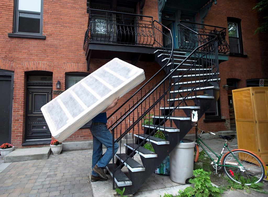 "A man carries a boxspring up a set of stairs on what has become known as ""Moving Day"" in Montreal on July 1, 2013."