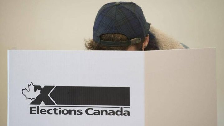 A woman marks her ballot behind a privacy barrier in the riding of Vaudreuil-Soulanges, west of Montreal, on October 19, 2015. THE CANADIAN PRESS IMAGES/Graham Hughes.