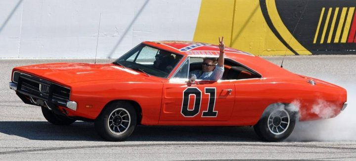 """ActorJohn Schnieder star of the 1980's U.S. television show The Dukes of Hazzard, waves from the General Lee before the Kobalt Tools 500 auto race Sunday, March 9, 2008, at Atlanta Motor Speedway in Hampton, Ga. Saskatchewan Premier Scott Moe says he meant no offence by retweeting a photo of a """"Dukes of Hazzard""""-inspired car adorned with the Confederate flag. THE CANADIAN PRESS/AP-Dale Davis."""
