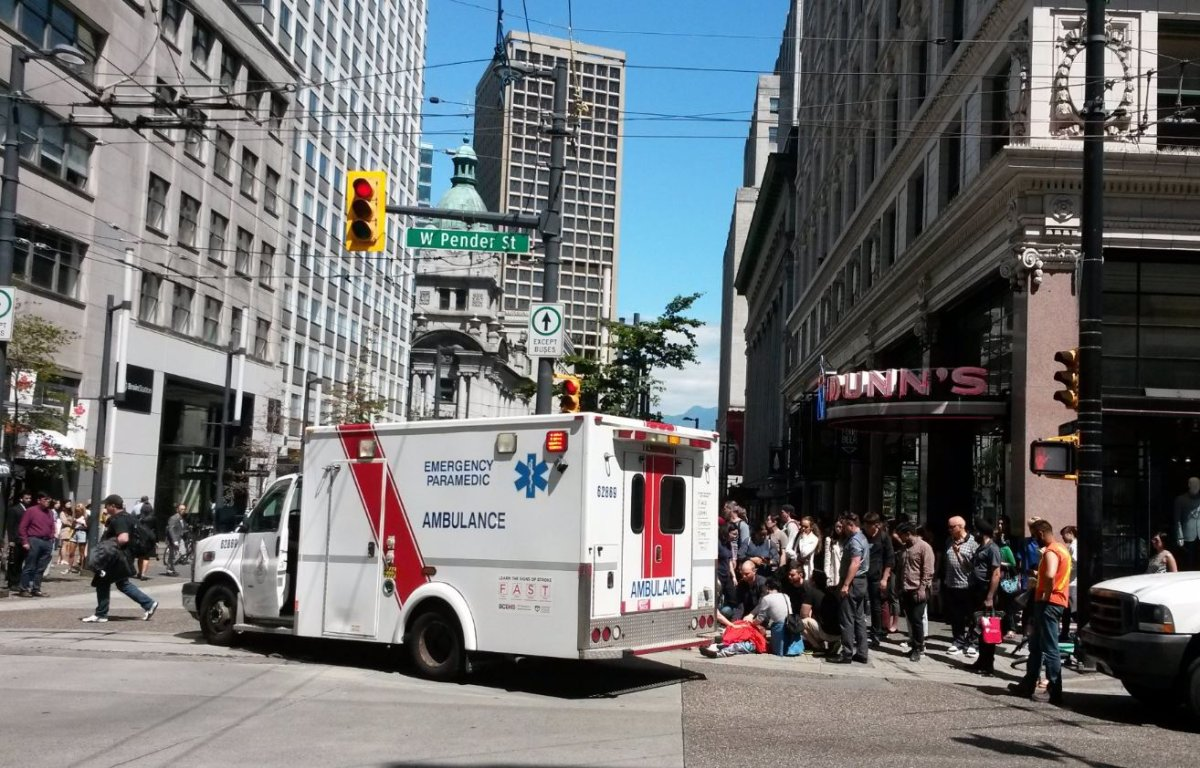 Paramedics on scene of a hit-and-run that injured a cyclist on Granville Street and Pender Street in downtown Vancouver Thursday, July 25, 2019.