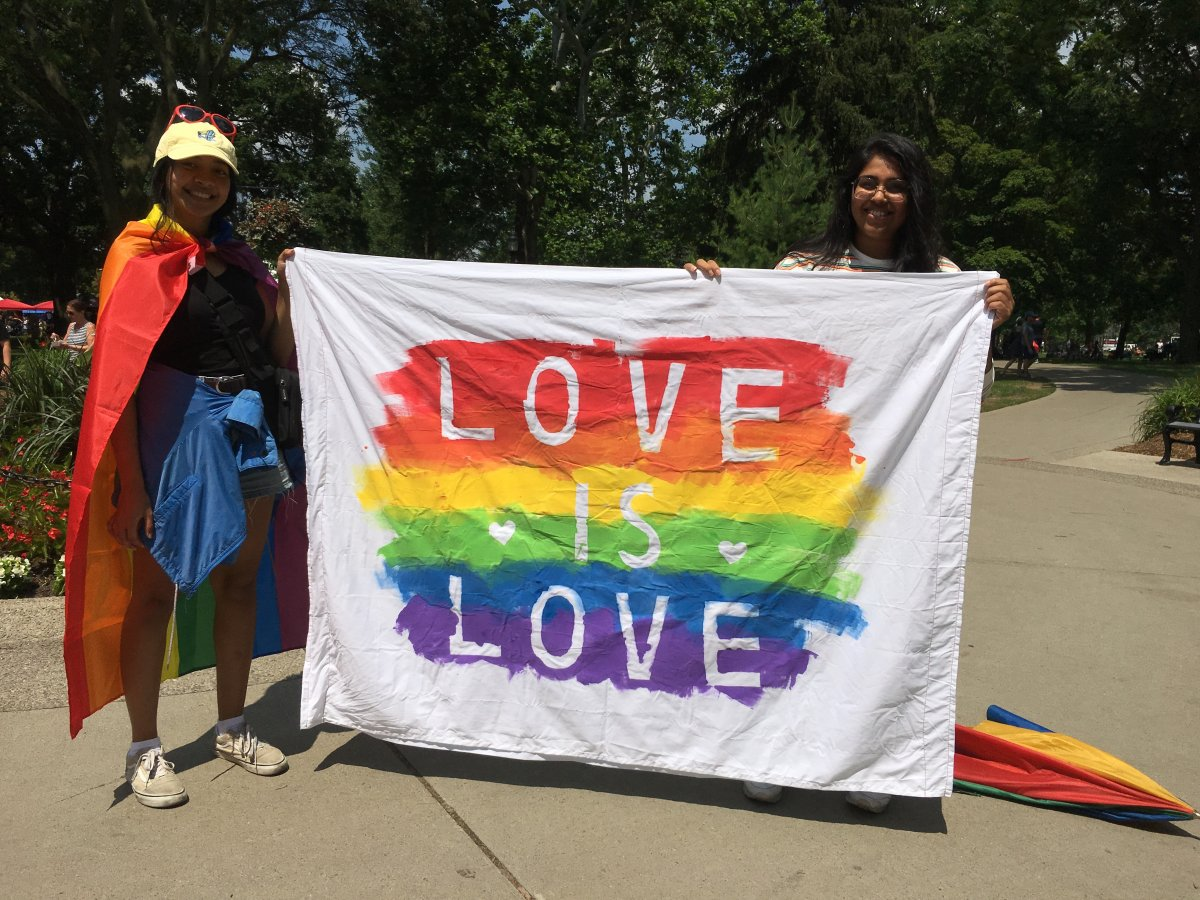 Dimple (right) and Fariah (left) showcase their homemade DIY flag at the 25th Pride Parade.