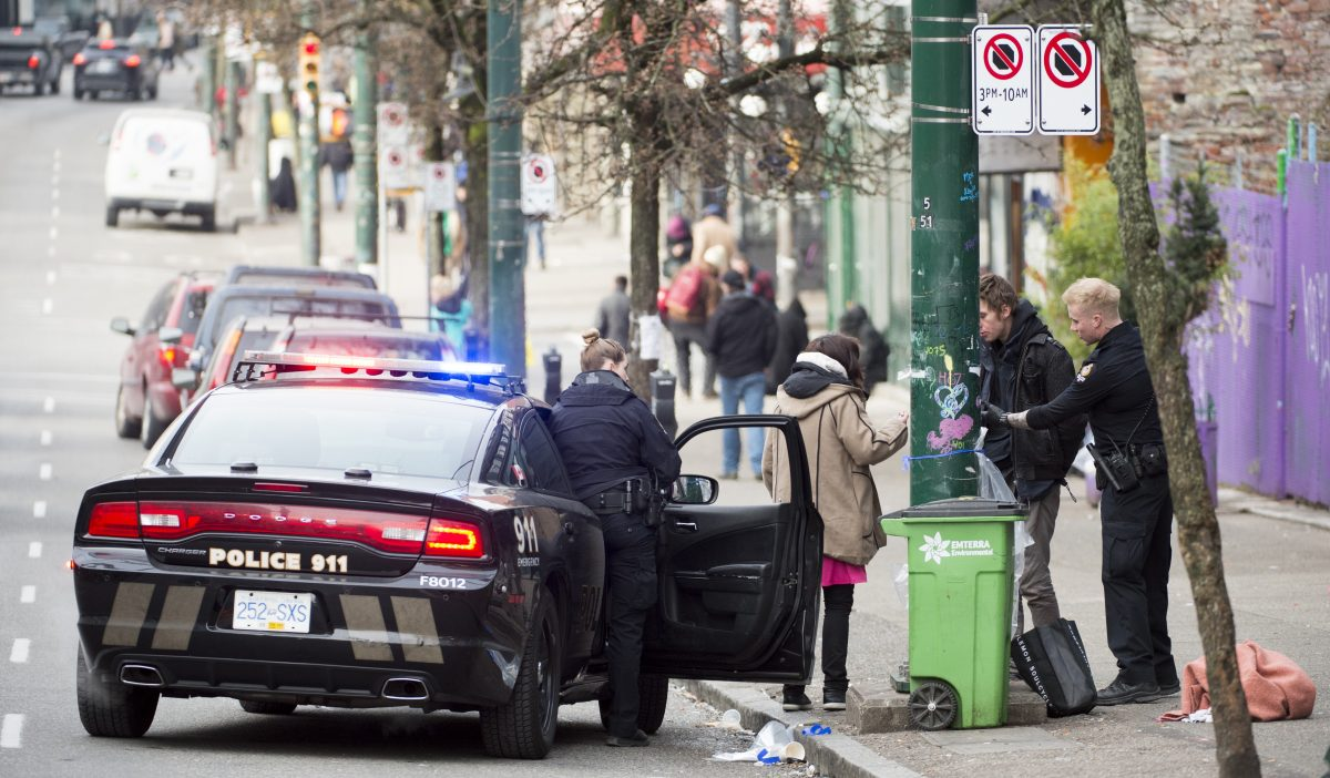 Police speak to a man and woman on East Hastings in Vancouver's downtown eastside, Thursday, Feb 7, 2019. More people fatally overdosed in British Columbia last year compared with 2017 despite efforts to combat the province's public health emergency, the coroner says.