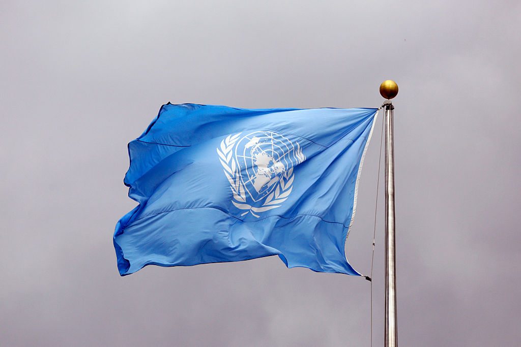 NEW YORK CITY, UNITED STATES - SEPTEMBER 24: Flag of the United Nations in front of grey clouds on top of the United Nations Secretariat at the headquarters of the United Nations on September 24, 2014, in New York City, United States.