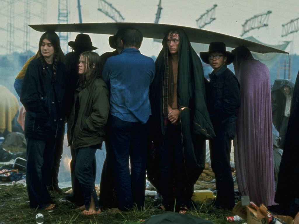 A sodden group, seeking shelter from rain, using a sheet of plywood as a makeshift umbrella, at the iconic Woodstock 1969 music festival.