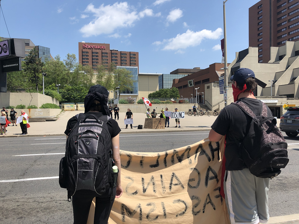 Pride supporters hold up signs across the street from Yellow Vest protesters in front of Hamilton city hall during a Pride rally earlier this month.