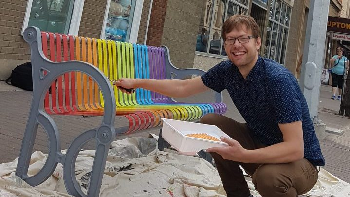 Benches in Moose Jaw were painted in rainbow colours to create awareness and discussion around the LGBTQ community. Wickenhauser is pictured painting one on Main Street in Moose Jaw.