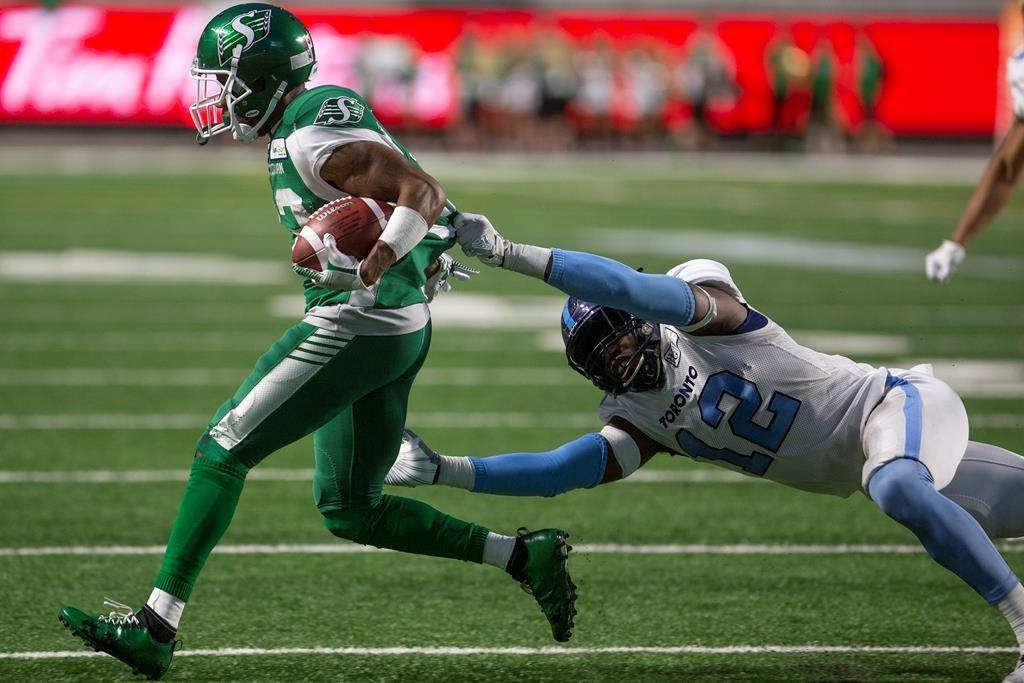 Saskatchewan Roughriders wide receiver Christion Jones (22) runs the ball as Toronto Argonauts linebacker Nelkas Kwemo (12) grabs onto his jersey during second half CFL football action in Regina on Monday, July 1, 2019.