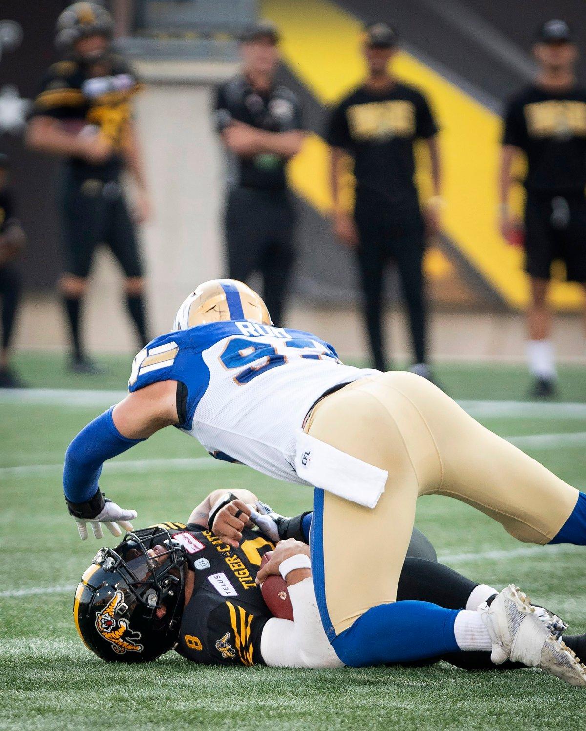 Winnipeg Blue Bombers defensive lineman Craig Roh goes over Hamilton Tiger-Cats quarterback Jeremiah Masoli during first half of game at Tim Hortons Field.
