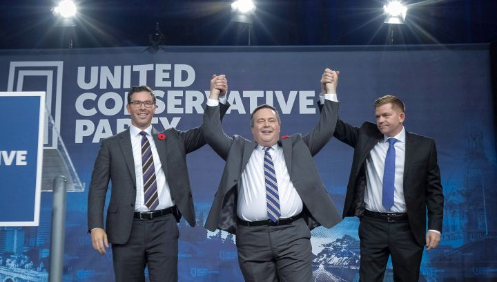 Brian Jean Jason Kenney, centre, celebrates his victory as the first official leader of the Alberta United Conservative Party with his opponents Brian Jean, right, and Doug Schweitzer in Calgary, Alta., Saturday, Oct. 28, 2017.