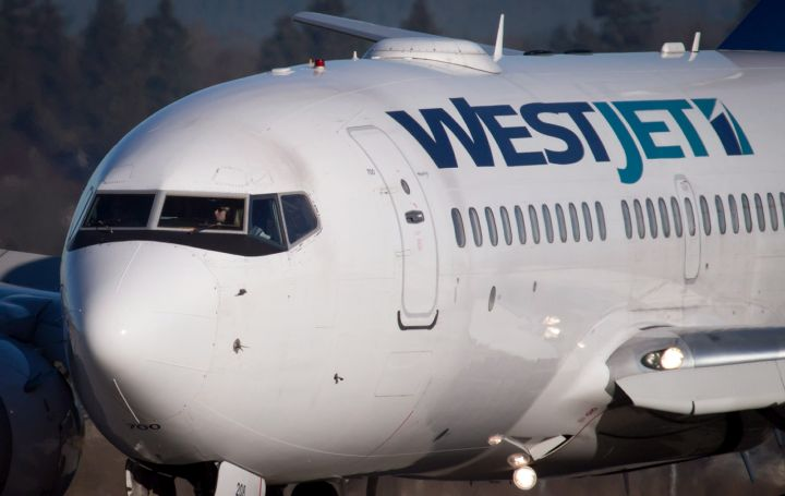 A pilot taxis a Westjet Boeing 737-700 plane to a gate after arriving at Vancouver International Airport in Richmond, B.C., on Monday, Feb. 3, 2014.
