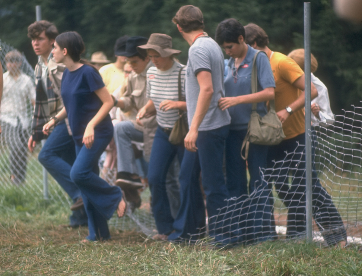 View of a group of people as they step over a torn-down fence in order to enter the grounds of the Woodstock Music & Art Festival, Bethel, N.Y., in Aug. 1969.