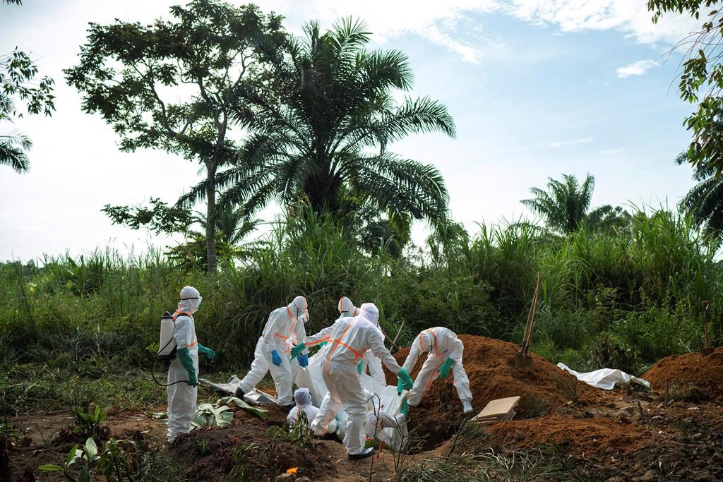In this Sunday, July 14, 2019 photo, workers bury the remains of Mussa Kathembo, an Islamic scholar who had prayed over those who were sick in Beni, Congo. Kathembo died of Ebola.