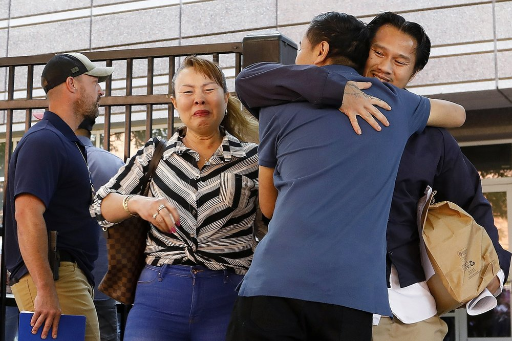 In this Wednesday, June 12, 2019 photo, Ammala Mingsouan embraces family outside the building that houses Immigration and Customs Enforcement and the Atlanta Immigration Court after being released from ICE custody, in Atlanta. Mingsouan's mother Littun Saenbouttaiath, right, said she had not seen him for 24 years.