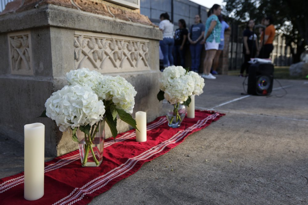 An altar of candles and white hydrangea flowers stands in memoriam of the 22 victims of the recent El Paso shooting during a vigil Sunday, Aug. 11, 2019, at Alice Wilson Hope Park in Brownsville, Texas.