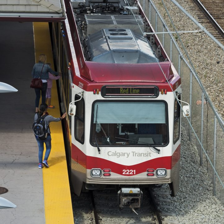 "Commuters board a Calgary Transit light rail (LRT) C-Train at Fish Creek-Lacombe station on the transit system's ""Red Line,"" Calgary, Alberta, August 24, 2016."