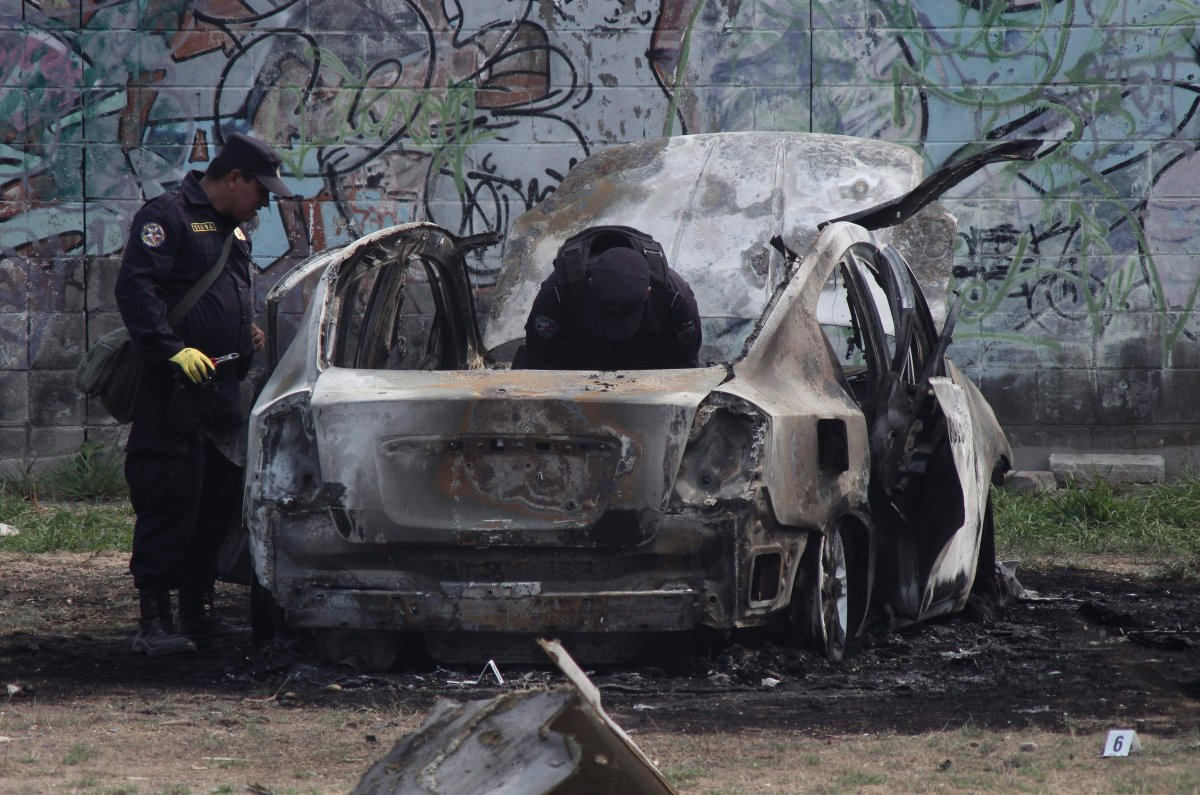 Police review the charred remains of a car that exploded as authorities responded to a report of a vehicle with a corpse inside, in the San Bartolo neighborhood of Soyapango, El Salvador, Monday, April 29, 2019.