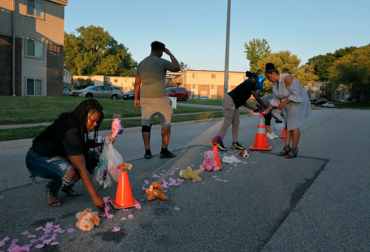 Cori Bush, left, drops paper rose petals around a memorial to Michael Brown on Canfield Drive in Ferguson, Mo., as she and others members of the community rebuild the memorial where Brown was shot and killed by Ferguson Police officer Darren Wilson, on Wednesday, Aug. 7, 2019.