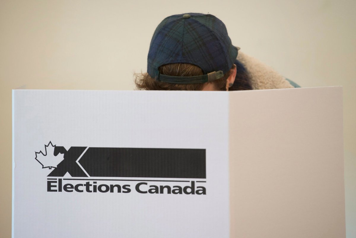 A voter marks a ballot behind a privacy barrier in the riding of Vaudreuil-Soulanges, west of Montreal, on election day, Monday, Oct. 19, 2015. Refugees in 2015, some Syrians are now citizens in time to vote in the 2019 federal election.