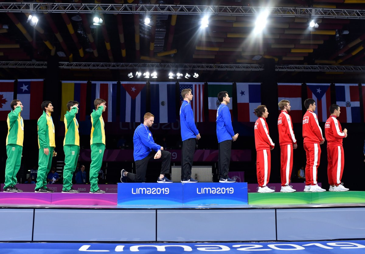 In this Friday, Aug. 9, 2019 photo, released by Lima 2019 News Services, Race Imboden of the United States takes a knee, as teammates Mick Itkin and Gerek Meinhardt stand on the podium after winning the gold medal in team's foil, at the Pan American Games in Lima, Peru.