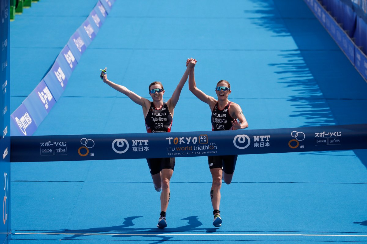 Britain's Georgia Taylor-Brown, left, and Jessica Learmonth hold hands as they cross the finish line during a women's triathlon test event at Odaiba Marine Park, a venue for marathon swimming and triathlon at the Tokyo 2020 Olympics, Thursday, Aug. 15, 2019, in Tokyo.