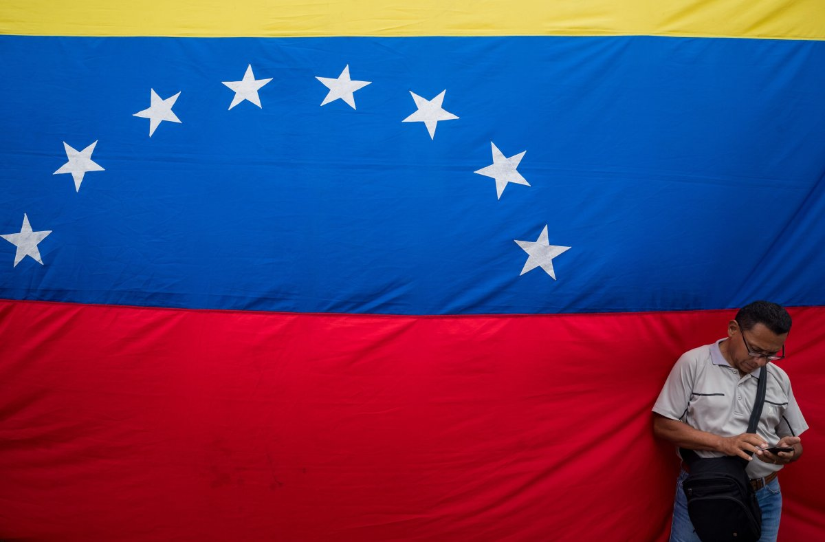 A man stands next to a Venezuelan flag as he looks at his cellphone during a signature collection event against the US blockade in Caracas, Venezuela, 15 August 2019. The President of Venezuela Nicolas Maduro suspended the talks with the opposition due to Juan Guaido's support of the blockade allegedely ordered by US President Donald Trump.