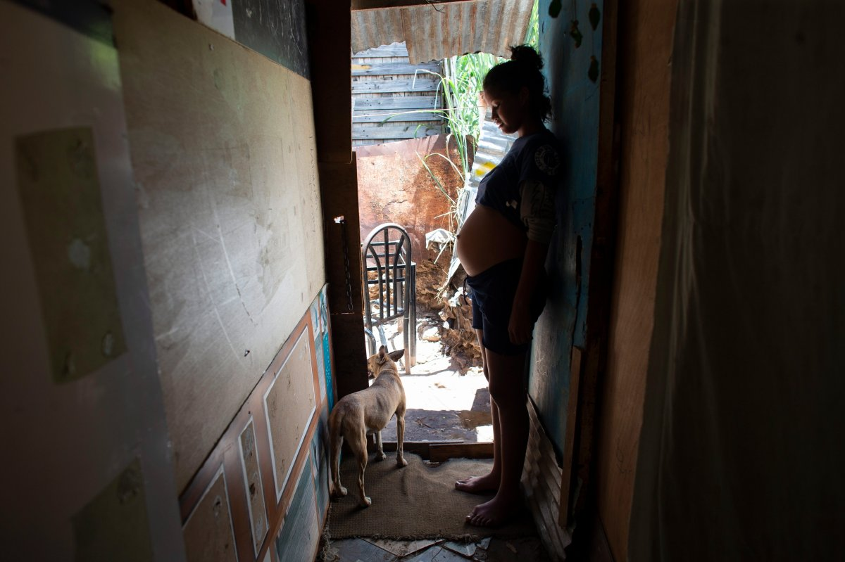 In this photo taken Aug. 5, 2019, 14-year-old Rosibeth Vargas, who is seven months pregnant, stands inside her home where she lives with her parents, 18-year-old sister and nephew, in the Tablitas area of the Caucaguita neighborhood on the outskirts of Caracas, Venezuela.