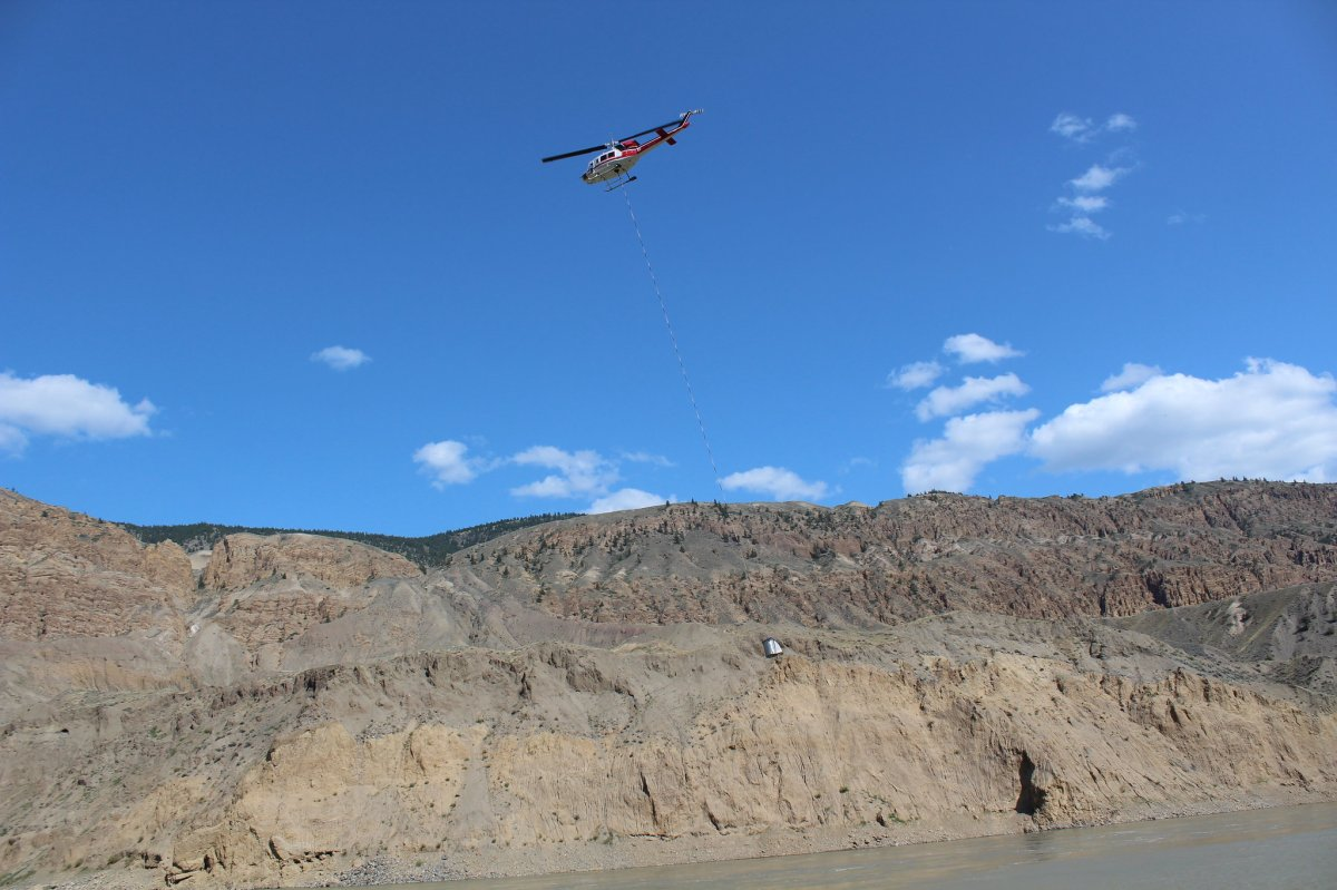 A helicopter moves a transport tank filled with salmon upstream of the landslide in the Fraser River near Big Bar, B.C. on Aug. 12, 2019.