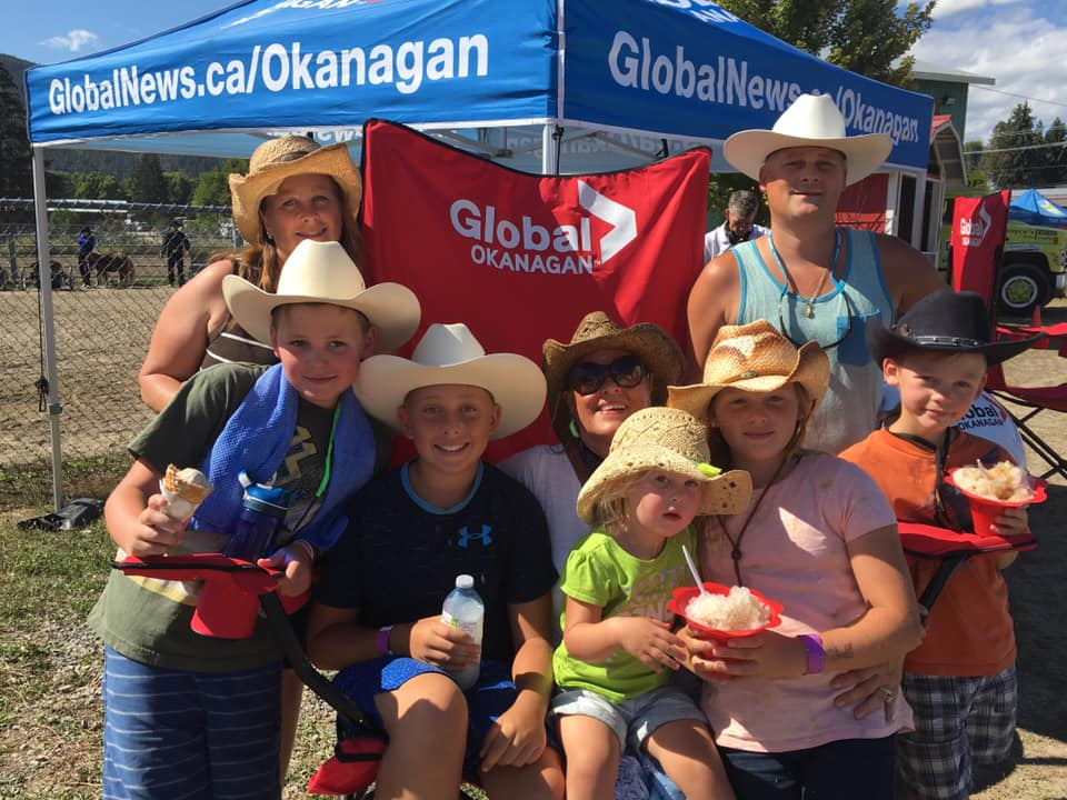 A family takes in the Global News #bigredchair at the Interior Provincial Exhibition in Armstrong on Wednesday.