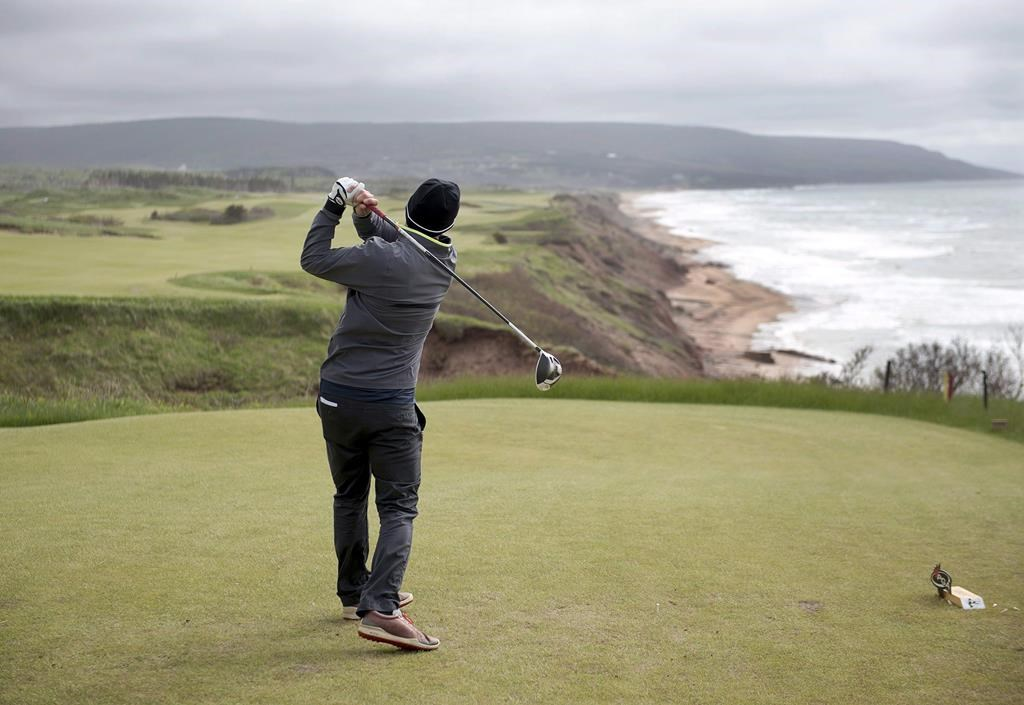 A golfer hits from the tee on the 528 yard, par 5, 18th hole at Cabot Cliffs, the seaside links golf course in Inverness, N.S. on June 1, 2016.