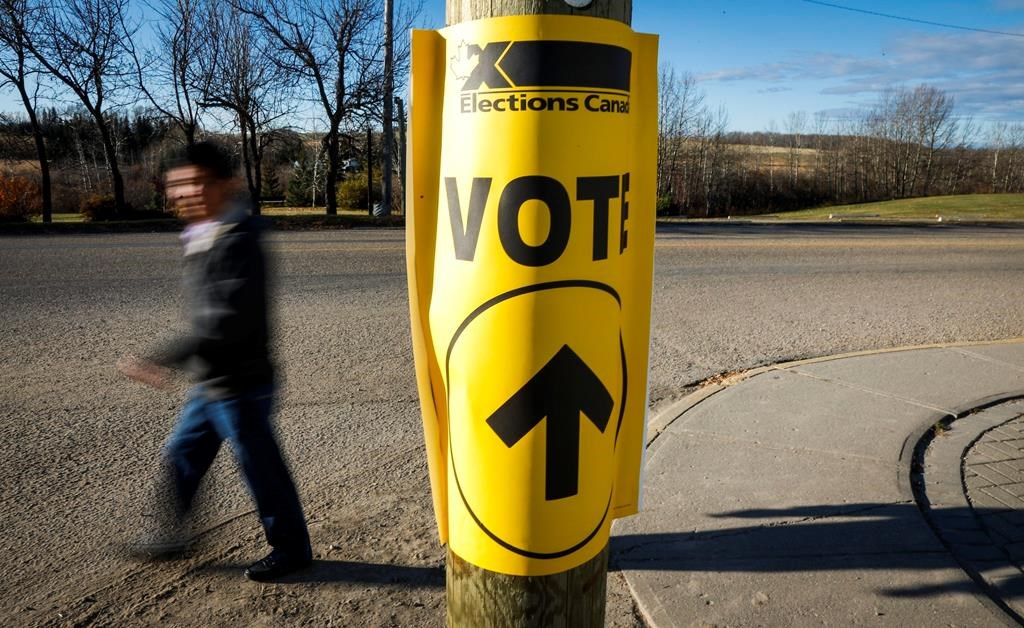 Canadians will be asked this fall to choose between moving forward with the Liberals or getting ahead with the Conservatives. A voter walks past a sign directing voters to a polling station for the Canadian federal election in Cremona, Alta., Monday, Oct. 19, 2015.