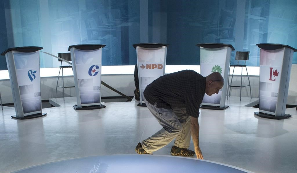 A technician cleans the set in preparation for a leaders debate, Wednesday, September 23, 2015 in Montreal. Leaders of five major parties have received invitations to participate in federal leaders' debates in October, with the People's Party of Canada left out for now.THE CANADIAN PRESS/Paul Chiasson.