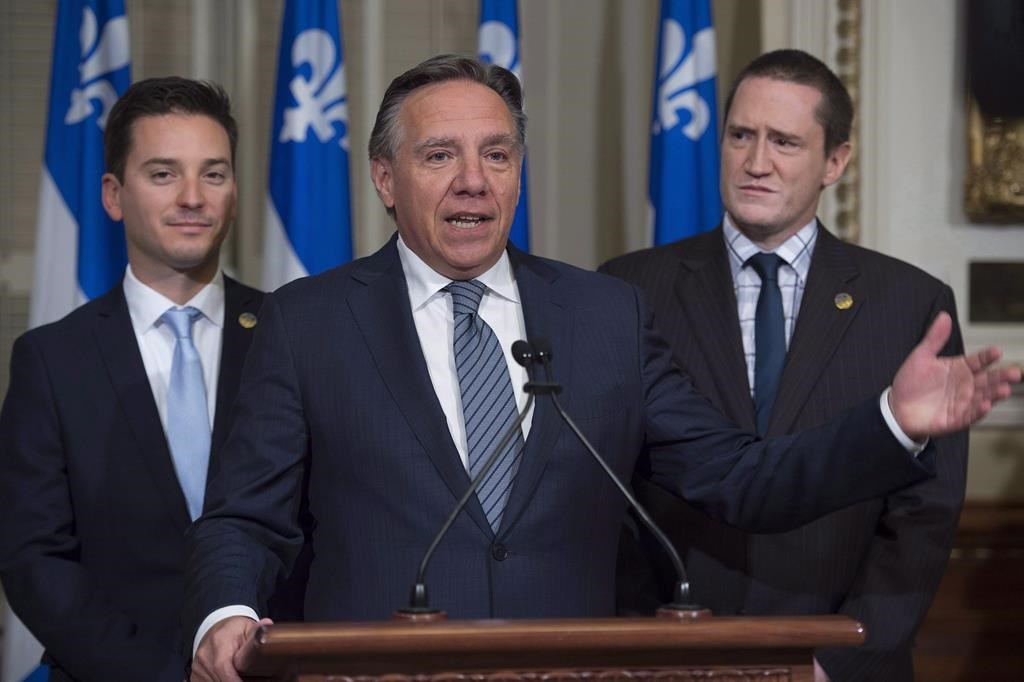 Coalition Avenir Quebec Leader Francois Legault speaks to reporters at a news conference prior to a party caucus meeting at the legislature in Quebec City, Oct. 19, 2016. MNAs Simon Jolin-Barrette, left, and Benoit Charrette look on. THE CANADIAN PRESS/Jacques Boissinot.