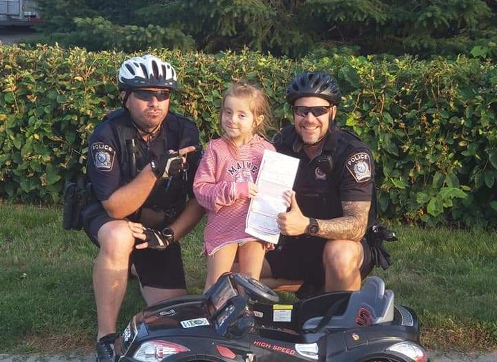Two Saint-Jérôme police officers pose with six-year-old Mélodie Cherkezian after jokingly writing her up for using her phone while driving.