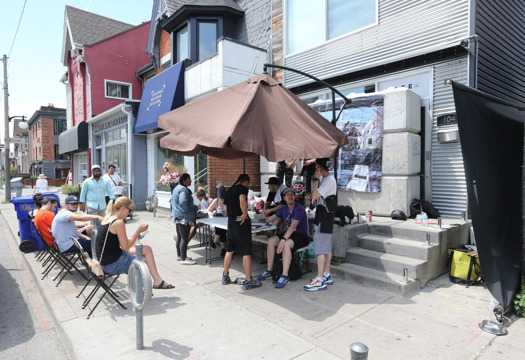 Tables and chairs and people with iPads line the sidewalk after local officials replaced the blocks in front of a grey-market dispensary at 104 Harbord St. in Toronto.