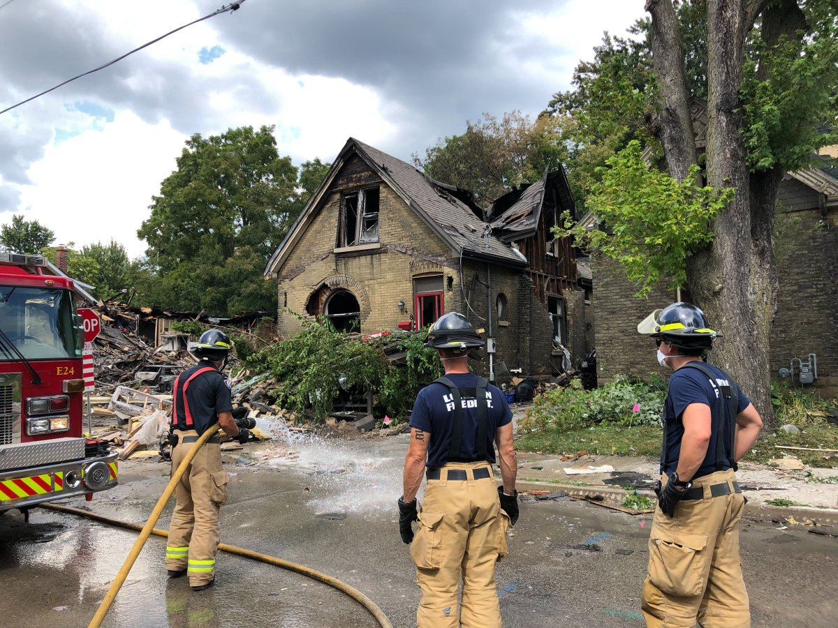 Firefighters in London, Ont., clean the street in front of 448 Woodman Avenue as they prepare the home for demolition.