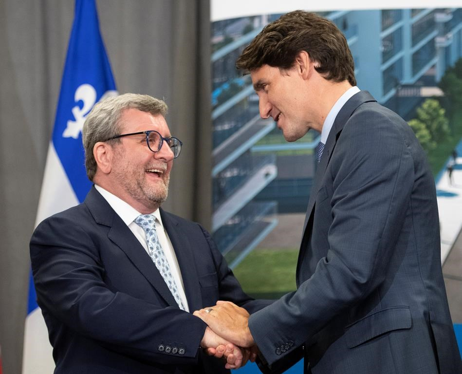 Prime Minister Justin Trudeau, right, shakes hand with Quebec City mayor Regis Labeaume after they announced a major investment for a tramway, Monday, August 19, 2019 in Quebec City.