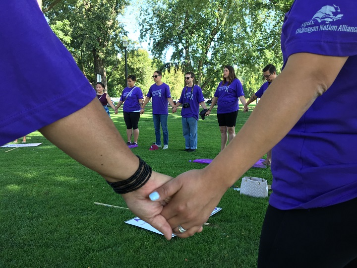 Members of the Purple Ribbon Campaign Caravan hold hands while gathering in City Park in Kelowna on Wednesday morning. The goal of two-day campaign is to raise awareness, educate people about addiction.  .