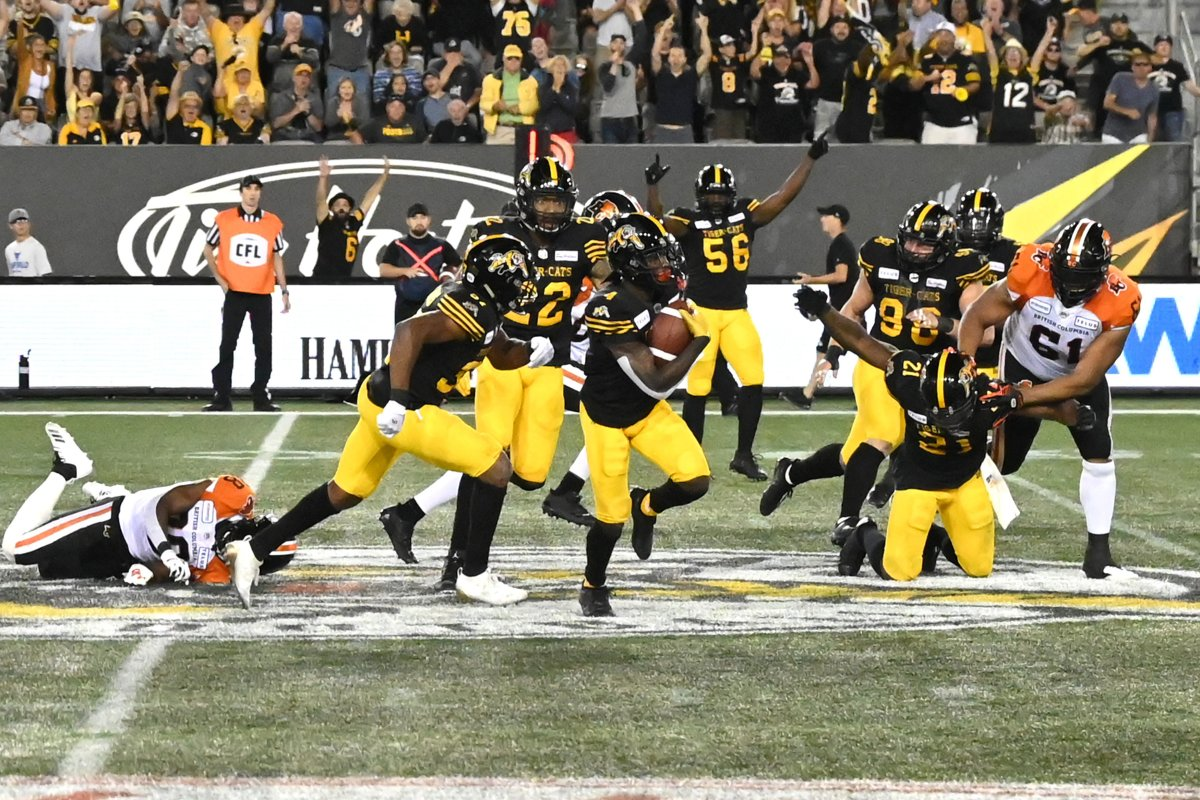 Hamilton Tiger-Cats' defensive back Richard Leonard, centre, runs back his interception in the final minute against the BC Lions during second half CFL football game action in Hamilton, Ontario on Saturday, August 10, 2019.