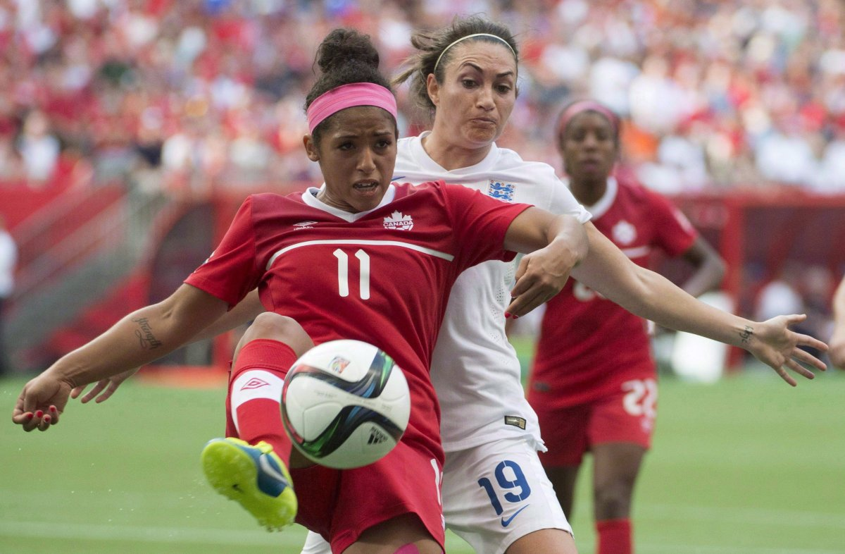 Canada's Desiree Scott, left, fights for the ball with England's Jodie Taylor during second half of FIFA World Cup quarter-final soccer action, in Vancouver on June 27, 2015.