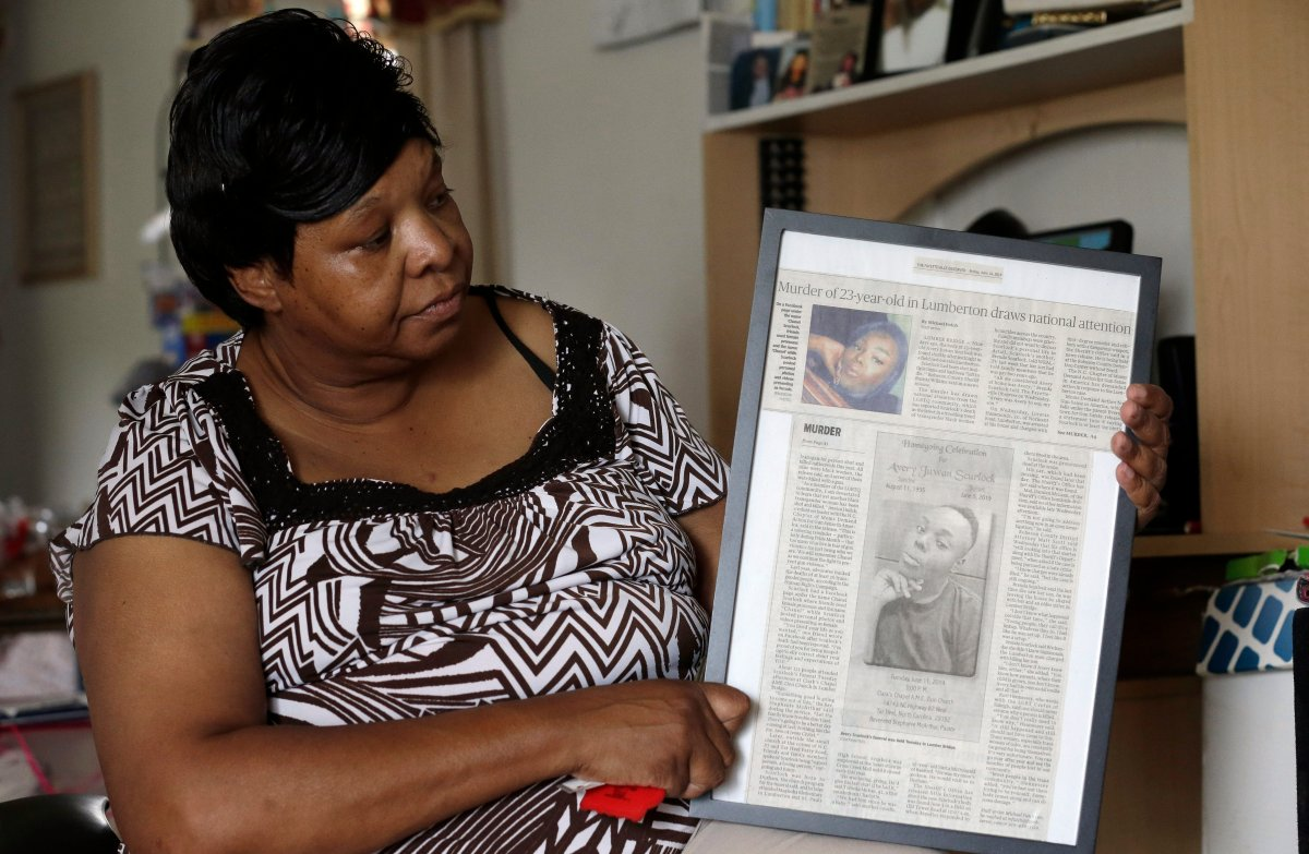In this photo taken Tuesday, Aug. 6, 2019 Brenda Scurlock is shown in her home in Lumber Bridge, N.C. holding a newspaper clipping about her son's murder. Scurlock's son Avery Scurlock, who used the name Chanel when dressing as a woman in social settings and hoped to have sex reassignment surgery,  was found shot to death in June. This death of a transgender person in North Carolina is one of 18  so far this year, and  17  of the victims have been black women.