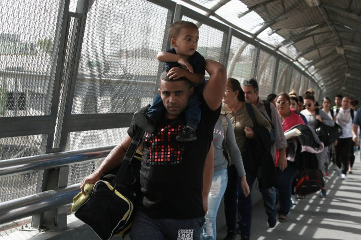 FILE - In this April 29, 2019 file photo, Cuban migrants are escorted by Mexican immigration officials in Ciudad Juarez, Mexico, as they cross the Paso del Norte International bridge to be processed as asylum seekers on the U.S. side of the border.