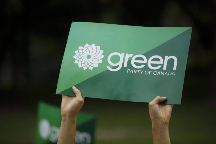 A supporter holds a sign for the Green Party of Canada in Toronto, Tuesday, Sept. 3, 2019.