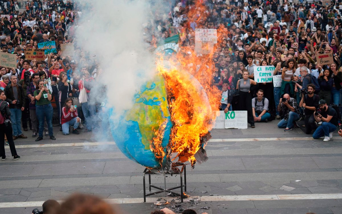 Students set fire to a replica of the planet Earth during a worldwide protest demanding action on climate change, in Milan, northern Italy, Friday, Sept. 27, 2019.
