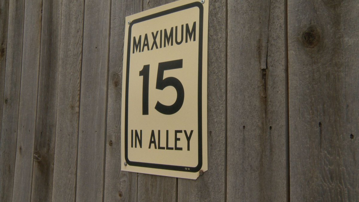 Speed limit sign posted at an alley in McKenzie Towne in Calgary .