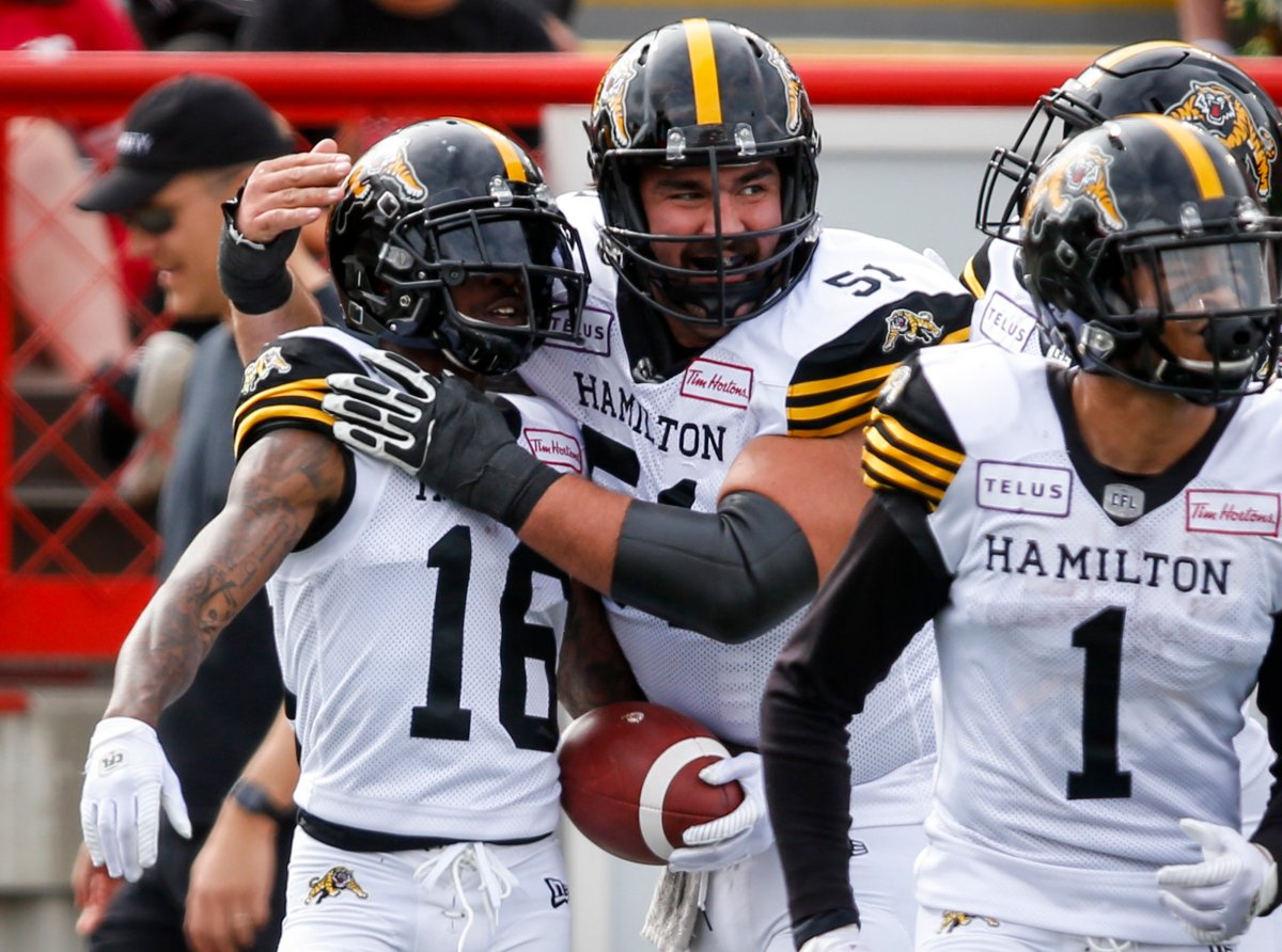 The Hamilton Tiger-Cats became the first team in the CFL this season to clinch a playoff spot after beating the Edmonton Eskimos 30-27 Friday night.
