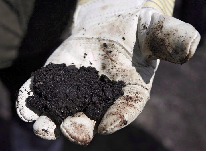 An oil worker holds raw sand bitumen near Fort McMurray, on July 9, 2008. Melius Energy says it has successfully tested a new technology that allows oilsands bitumen to be shipped as a semi-solid product in six-metre-long shipping containers.