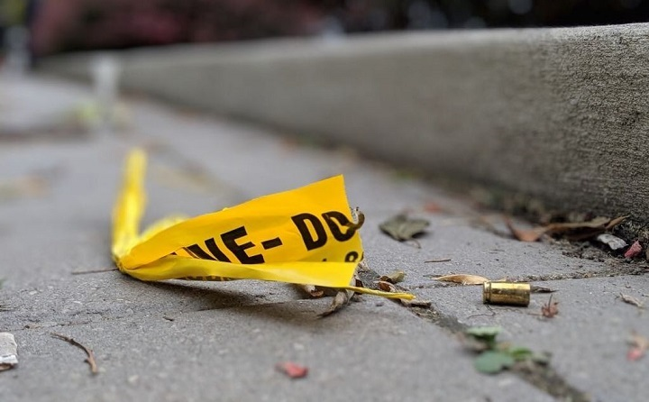 A shell casing is seen next to police tape.