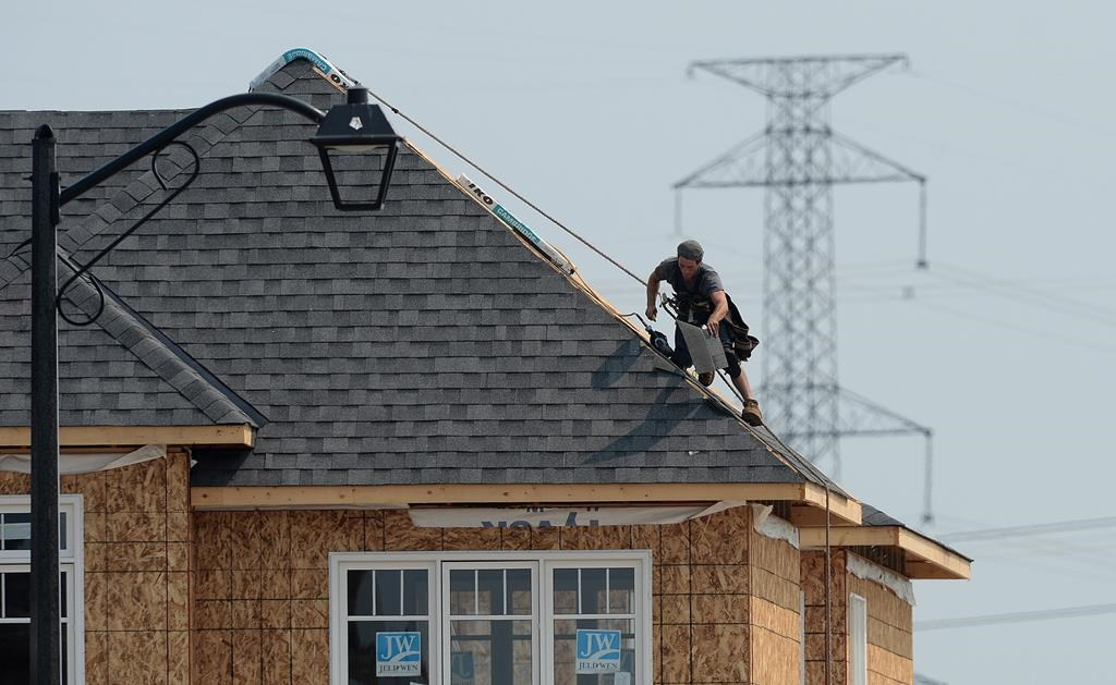 A construction worker shingles the roof of a new home in a housing development in Ottawa on Monday, July 6, 2015.