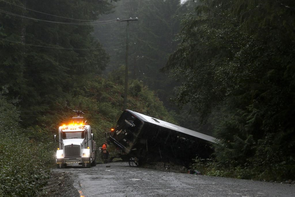 A tow-truck crew removes a bus from an embankment next to a logging road near Bamfield, B.C., on Saturday, Sept. 14, 2019.