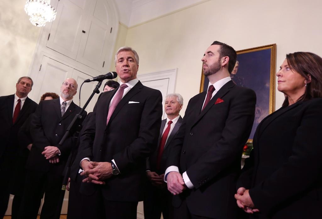 Newfoundland and Labrador Liberal Party Leader Dwight Ball, joined by members of his cabinet, Gerry Byrne, left to right, Perry Trimper, Eddie Joyce, Andrew Parsons and Siobahn Coady, speaks with the media after being sworn in as the province's 13th premier at Government House, in St. John's, N.L., on Monday, Dec. 14, 2015.